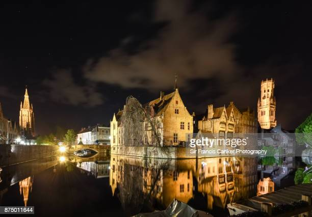 Belfry of Bruges, Church of our Lady spire and romantic Rozenhoedkaai canal illuminated at night in Flanders, Belgium