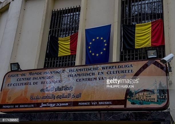 Belgian and EU flags arer displayed above the entrance to the Grand Mosque in Brussels on Match 25 as Muslims gathered for the first Friday prayers...