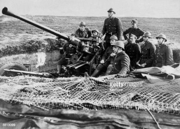 Belgian antiaircraft gun crew man their gun in its dugout near the German frontier