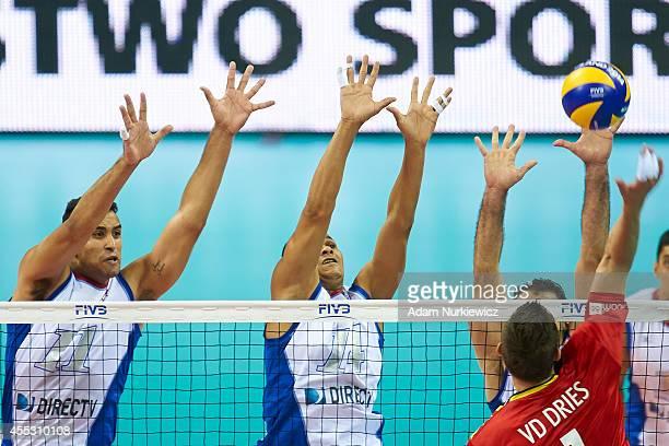 Belgian Bram Van Den Dries attacks against Puerto Rico's Maurice Torres and Mannix Roman during the FIVB World Championships match between Belgium...