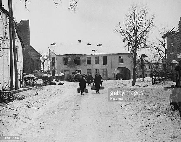 Belgian civilians carry suitcases down a snowy road as they evacuate the town of Amel during the Battle of the Bulge Belgium 1944 | Location Amel...