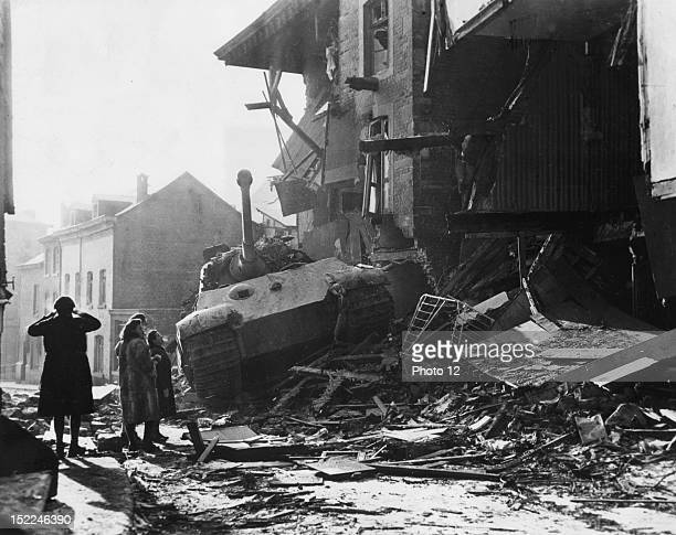 Belgian civilians examine a knocked out German VI Royal Tiger tank destroyed by US troops fighting in Stavelot during the Battle of the Bulge
