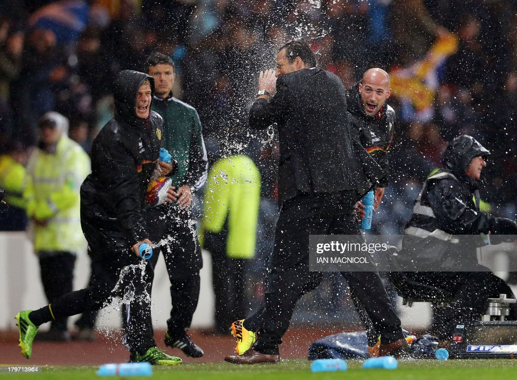 Belgian coaching staff celebrate at full time by throwing water at manager Mark Wilmots (3rd R) following the 2014 World Cup Group A qualifying football match between Scotland and Belgium at Hampden Park in Glasgow, Scotland, on September 6, 2013. AFP PHOTO / IAN MACNICOL