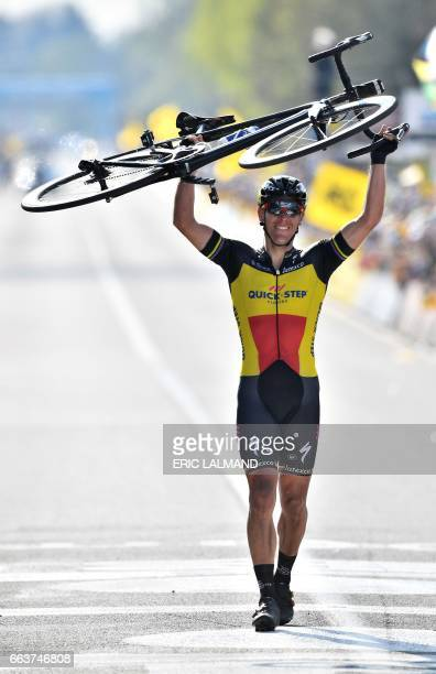 Belgian cyclist Philippe Gilbert of Quick-Step Floors raises his bike as he crosses the finish line and win the 101st edition of the Ronde van...