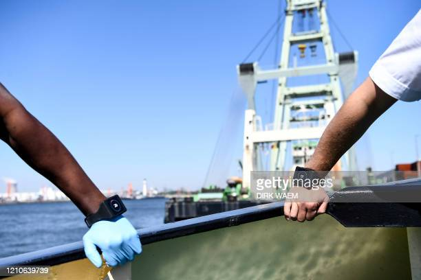 A Belgian deck hand and a captain wear a Romware Covid Radius bracelet during a presentation of the device at the Port of Antwerp on April 22 2020...
