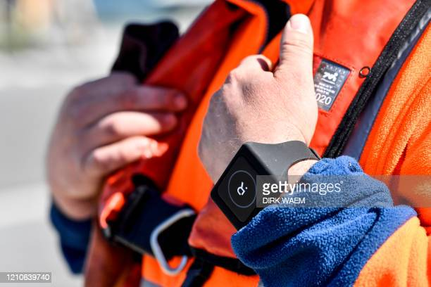 A Belgian deck hand wears a Romware Covid Radius bracelet during a presentation of the device at the Port of Antwerp on April 22 2020 The bracelet...