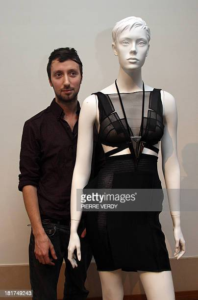 Belgian designer Anthony Vaccarello stands with one of his creations during the autumn-winter 2010 pret-a-porter collection show on March 2, 2010 in...