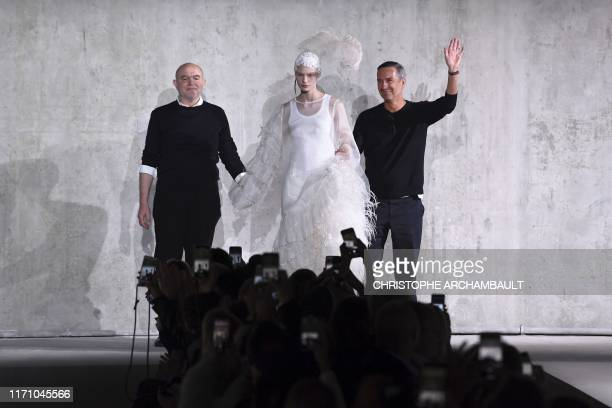 Belgian designer Dries Van Noten and French designer Christian Lacroix acknowlegde the audience after the Dries Van Noten fashion show during the...