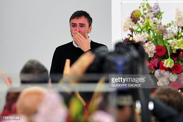 Belgian designer Raf Simons blows a kiss to the audience as he cries at the end of the Jil Sander Fall-winter 2012-2013 collection on February 25,...