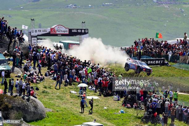Belgian driver Thierry Neuville and Belgian codriver Nicolas Gilsoul jump with their Hyundai i20 WRC in Fafe northern Portugal on May 21 during the...