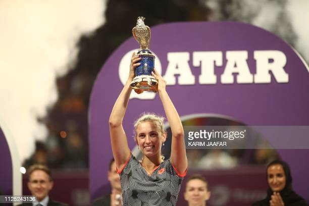Belgian Elise Mertens poses with the trophy after her victory over Romanian Simona Halep in their WTA Qatar Open final tennis match in Doha on...
