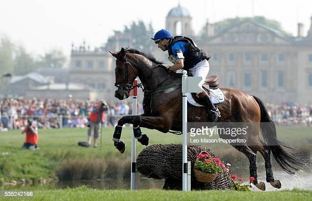 Belgian equestrian Joris Vanspringel riding Lully des Aulnes exits the lake complex with Badminton House in the background during competition in the...