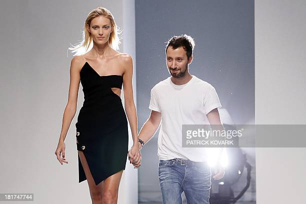 Belgian fashion designer Anthony Vaccarello acknowledges the public with Polish model Anja Rubik at the end of his 2014 Spring/Summer readytowear...