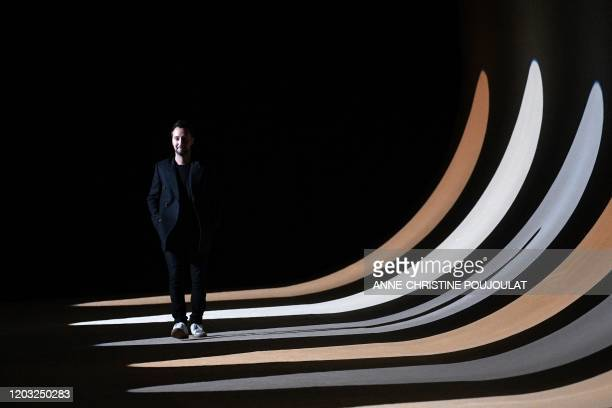 Belgian fashion designer for Yves Saint Laurent, Anthony Vaccarello, acknowledges the audience at the of the Women's Fall-Winter 2020-2021...
