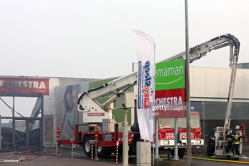 Belgian firefighters work at an industrial site in Oostende on February 13, 2013, where a fire started earlier during roofing construction works at baby specialty store Premama, and quickly spread to other buildings, without injuring any casualty, according to firefighters.