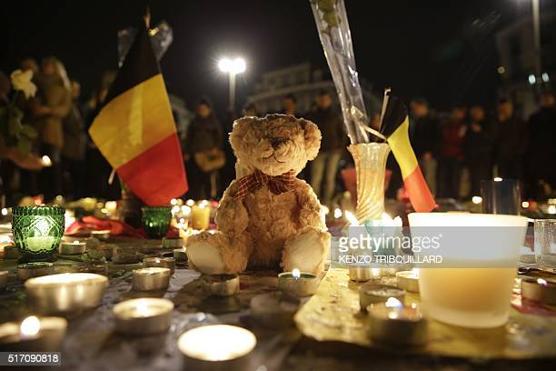 A Belgian flag candles and a Teddy bear are pictured as people gather at a makeshift memorial on the Place de la Bourse in Brussels on March 23 a day...
