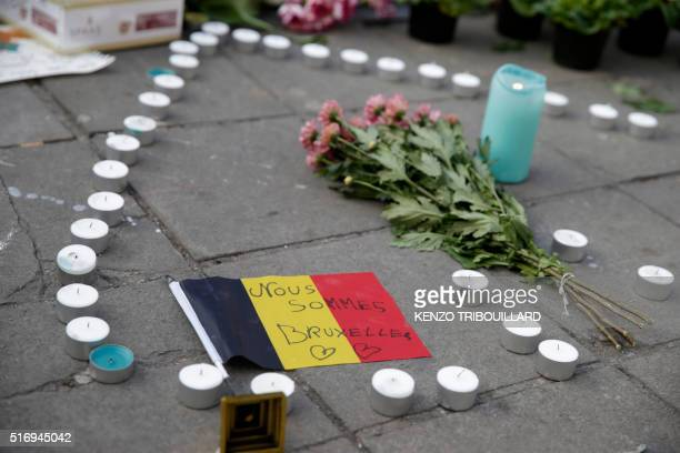 A Belgian flag reads We are all Brussels at a makeshift memorial at Place de la Bourse following attacks in Brussels on March 22 2016 Airlines...