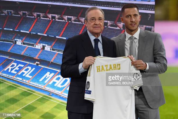 Belgian footballer Eden Hazard and Real Madrid's president Florentino Perez hold the midfielder's new jersey during his official presentation as new...