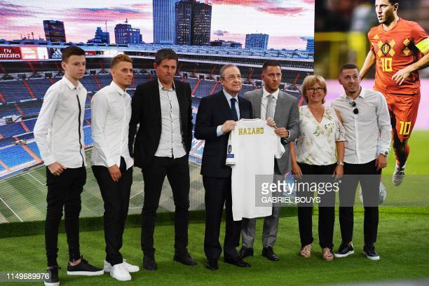 Belgian footballer Eden Hazard and Real Madrid's president Florentino Perez hold the midfielder's new jersey flanked by his family during his...