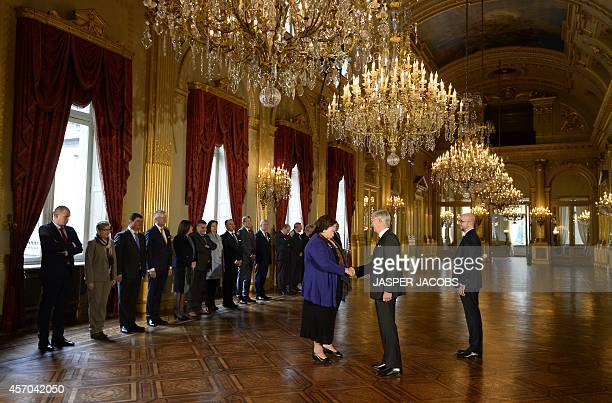 Belgian Health and Social Affairs Minister Maggie De Block shakes hands with Belgium's King Philippe next to new Belgian Prime Minister Charles...