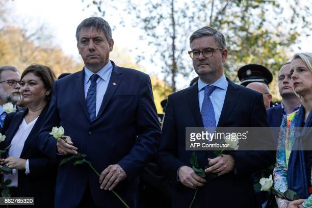 Belgian Interior Minister Jan Jambon and European Commissioner for the Security Union Julian King hold white roses during a ceremony in support of...