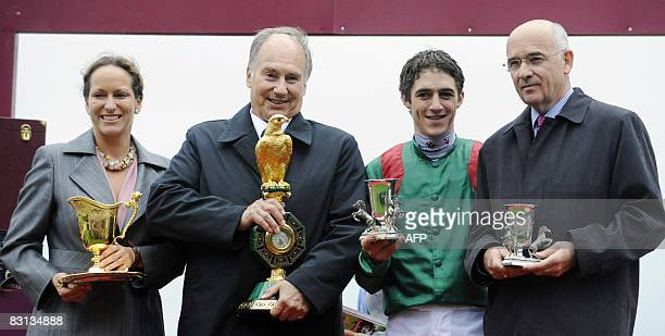 Belgian jockey Christophe Soumillon poses with his trophy after winning the 87th Prix de l'Arc de Triomphe race riding favorite filly Zarkava flanked...