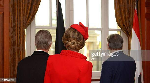 Belgian King Philippe, Queen Mathilde and Berlin's Mayor Klaus Wowereit look out of the window after signing the Golden Book of the city of Berlin at...