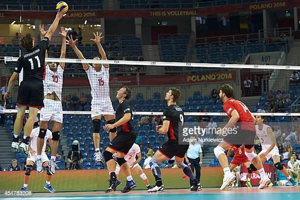 Belgian Matthijs Verhanneman attacks against Iran's Amir Ghafour and Armin Tashakori during the FIVB World Championships match between Belgium and...