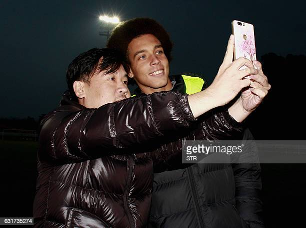 Belgian midfielder Axel Witsel takes a selfie with a Chinese fan during the warmup ahead of a warmup match between Tianjin Quanjian FC and Sichuan...
