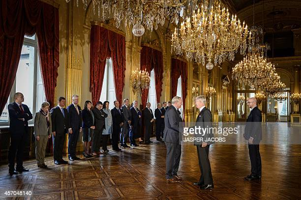 Belgian Minister of Budget Herve Jamar shakes hands with Belgium's King Philippe next to new Belgian Prime Minister Charles Michel during the...