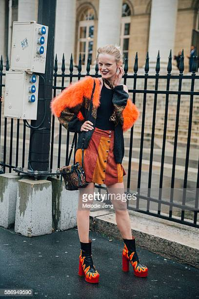 Belgian model Hanne Gaby wears a orange black and animal print fur sweater a red and orange suede striped buttonup skirt a paisleyprint purse and...
