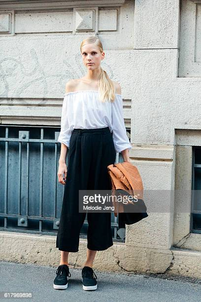Belgian model Kirin Dejonckheere wears an offshoulder white top black trousers and black sneakers after the Prada show during Milan Fashion Week...