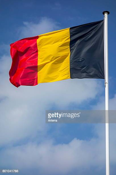 Belgian national flag of Belgium on flagpole flying in the wind against cloudy sky