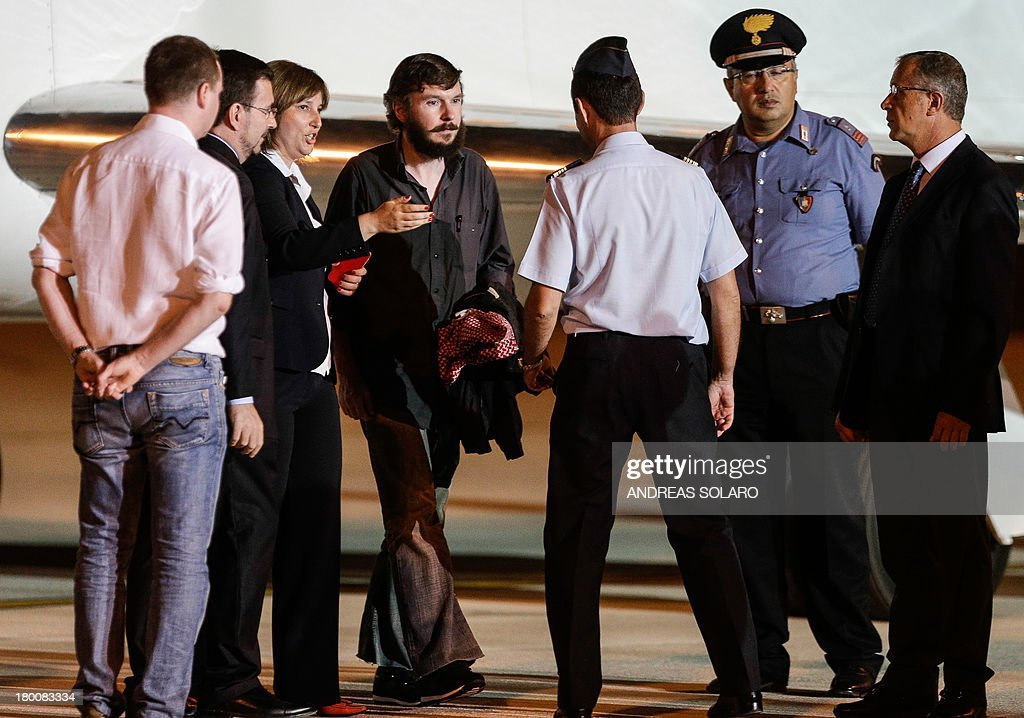 Belgian national Pierre Piccinin (4L) and italian journalist Domenico Quirico (unseen), both kidnapped in Syria in early April, disembark from the airplane on September 9, 2013 at Ciampino military airport in Rome.