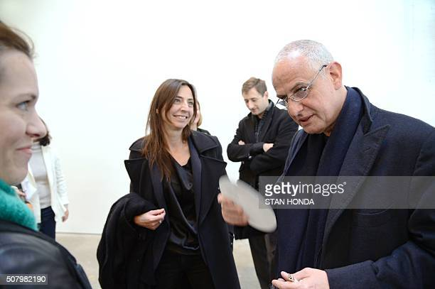 Belgian painter Luc Tuymans speaks with people at a preview of an exposition of his artwork January 10 2013 at the David Zwirner Gallery in New York...