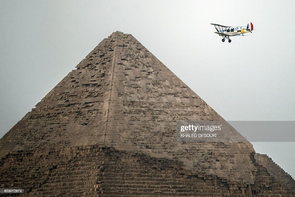 Belgian pilots Alexandra Maingard and her husband Cedric Collette fly their vintage Stampe OO-GWB biplane by one of the Pyramids of Giza, on the southern outskirts of the Egyptian capital Cairo on November 13, 2016 during the Vintage Air Rally (VAR). A dozen biplanes from the 1920s and 1930s are flying 8,000 miles from Crete to Cape Town in a vintage aviation rally that harks back to the early days of air travel. / AFP / KHALED