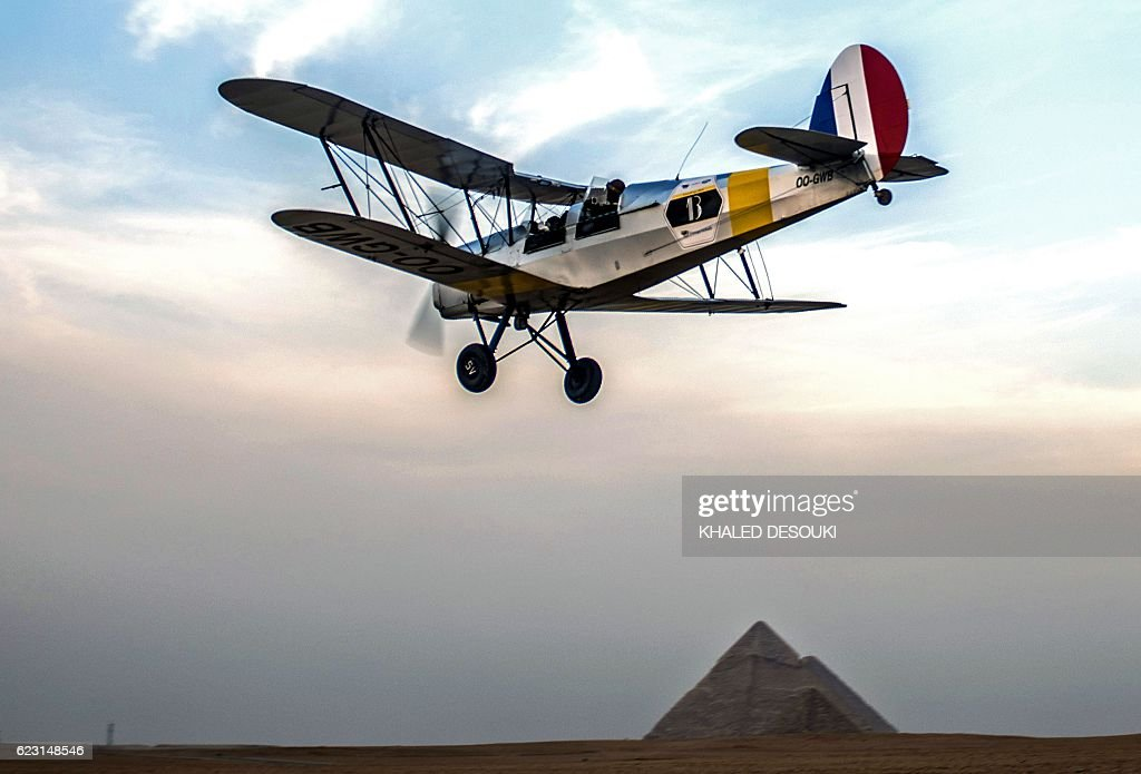 Belgian pilots Alexandra Maingard and her husband Cedric Collette fly their vintage Stampe OO-GWB biplane near the Pyramids of Giza, on the southern outskirts of the Egyptian capital Cairo on November 13, 2016 during the Vintage Air Rally (VAR). A dozen biplanes from the 1920s and 1930s are flying 8,000 miles from Crete to Cape Town in a vintage aviation rally that harks back to the early days of air travel. / AFP / KHALED
