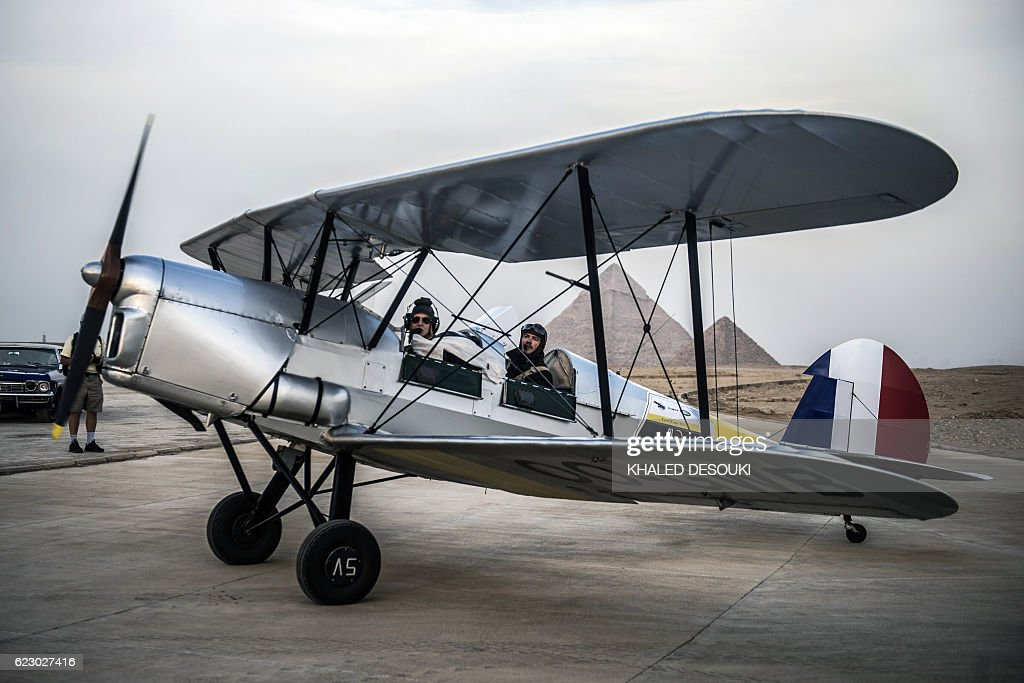 Belgian pilots Alexandra Maingard (L) and her husband Cedric Collette prepare their biplane for takeoff at an airfield near the Pyramids of Giza, on the southern outskirts of the Egyptian capital Cairo on November 13, 2016 during the Vintage Air Rally (VAR). A dozen biplanes from the 1920s and 1930s are flying 8,000 miles from Crete to Cape Town in a vintage aviation rally that harks back to the early days of air travel. The pilots will fly along the Nile from Cairo to Khartoum, past the highlands of Ethiopia, down through East Africa past Mount Kilimanjaro, over Victoria Falls, and will end in South Africa. It is the first aviation rally to be granted permission to land at Egypt's Giza pyramids in 50 years, and will put on Sudan's first air show. / AFP / KHALED