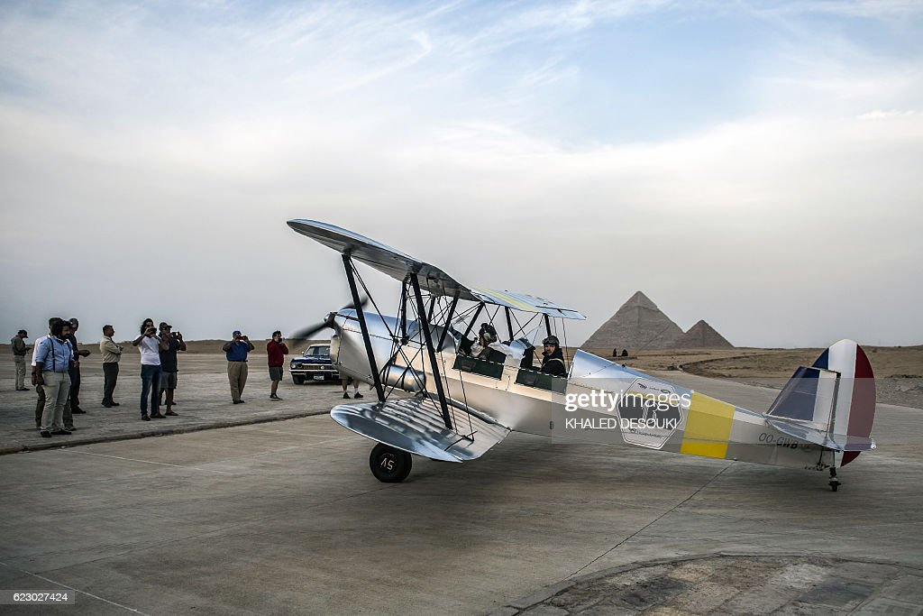 Belgian pilots Alexandra Maingard (L) and her husband Cedric Collette prepare their biplane for takeoff it an airfield near the Pyramids of Giza, on the southern outskirts of the Egyptian capital Cairo on November 13, 2016 during the Vintage Air Rally (VAR). A dozen biplanes from the 1920s and 1930s are flying 8,000 miles from Crete to Cape Town in a vintage aviation rally that harks back to the early days of air travel. The pilots will fly along the Nile from Cairo to Khartoum, past the highlands of Ethiopia, down through East Africa past Mount Kilimanjaro, over Victoria Falls, and will end in South Africa. It is the first aviation rally to be granted permission to land at Egypt's Giza pyramids in 50 years, and will put on Sudan's first air show. / AFP / KHALED