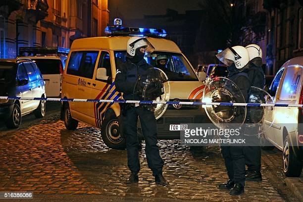Belgian police forces stand guard in a street during a police action in the MolenbeekSaintJean district in Brussels on March 18 2016 Belgian police...