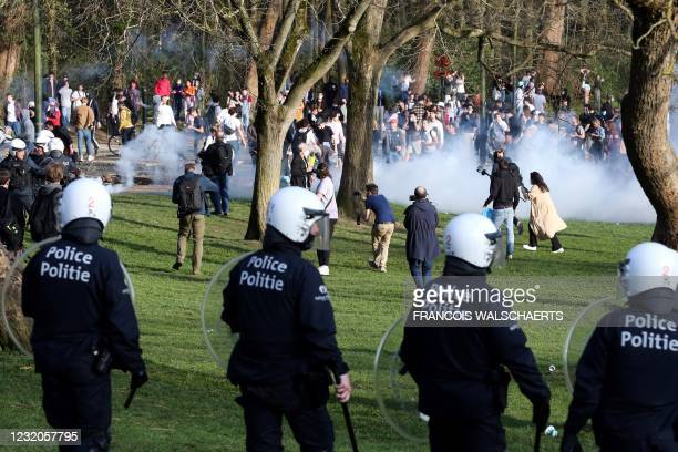 Belgian Police officers surround bystanders at the Bois de la Cambre parc, in Brussels, on April 1, 2021 during a unauthorised rally, for a fake...
