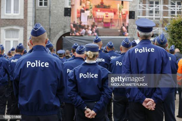 Belgian police officers watch a giant screen transmission of the funeral service for slain colleague Amaury Delrez as they stand outside at a church...