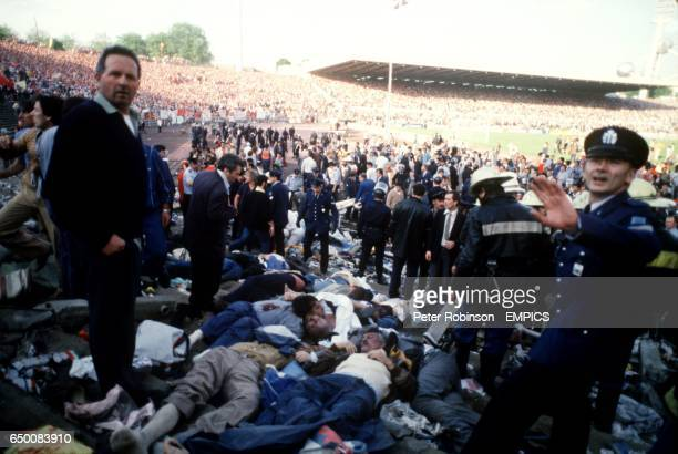 Belgian policemen mill around in the aftermath of the Heysel disaster unsure of how to proceed
