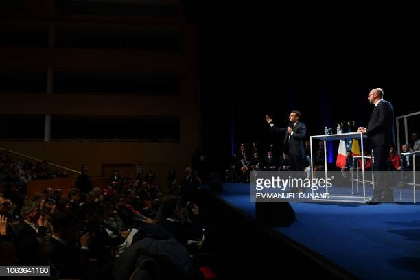 Belgian Prime Minister Charles Michel and French President Emmanuel Macron stand on stage during their visit at the University of Louvain on November...