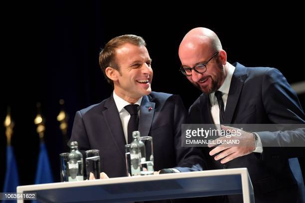 Belgian Prime Minister Charles Michel and French President Emmanuel Macron share a laugh during their visit at the University of Louvain on November...