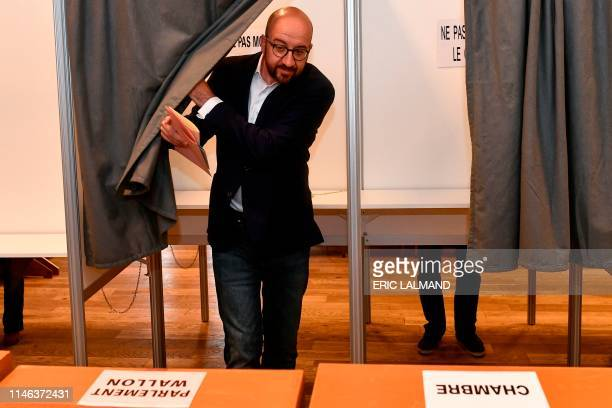 Belgian Prime Minister Charles Michel leaves a polling booth to cast his vote for the European elections at a polling station in Limal on May 26 2019...