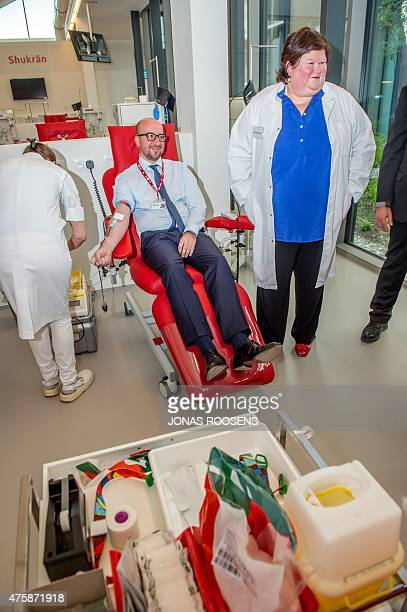 Belgian Prime Minister Charles Michel sits as he donates his blood, flanked and Belgian Minister of Health and Social Affairs Maggie De Block ,...