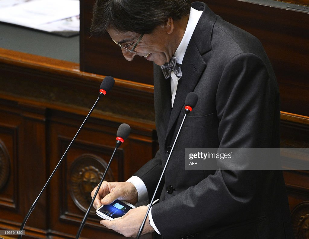 Belgian Prime Minister Elio Di Rupo switches off his cellular telephone as he addresses a plenary session of the federal parliament in Brussels on November 21, 2012, a day after his government comp...
