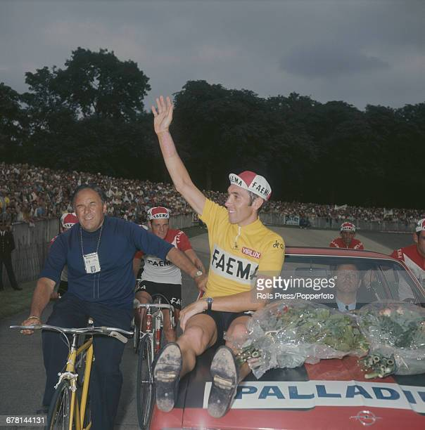 Belgian professional road race cyclist Eddy Merckx waves to the crowd after finishing in first place after the final time trial stage to win the 1969...