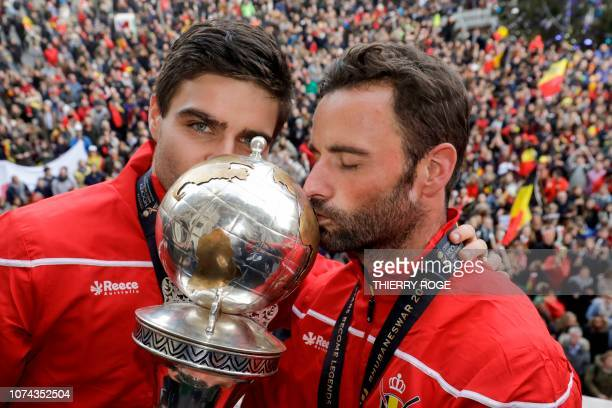Belgian Red Lions field hockey team's members Arthur De Sloover and Belgium's Sebastien Dockier kiss the Trophy after winner the World Cup on the...